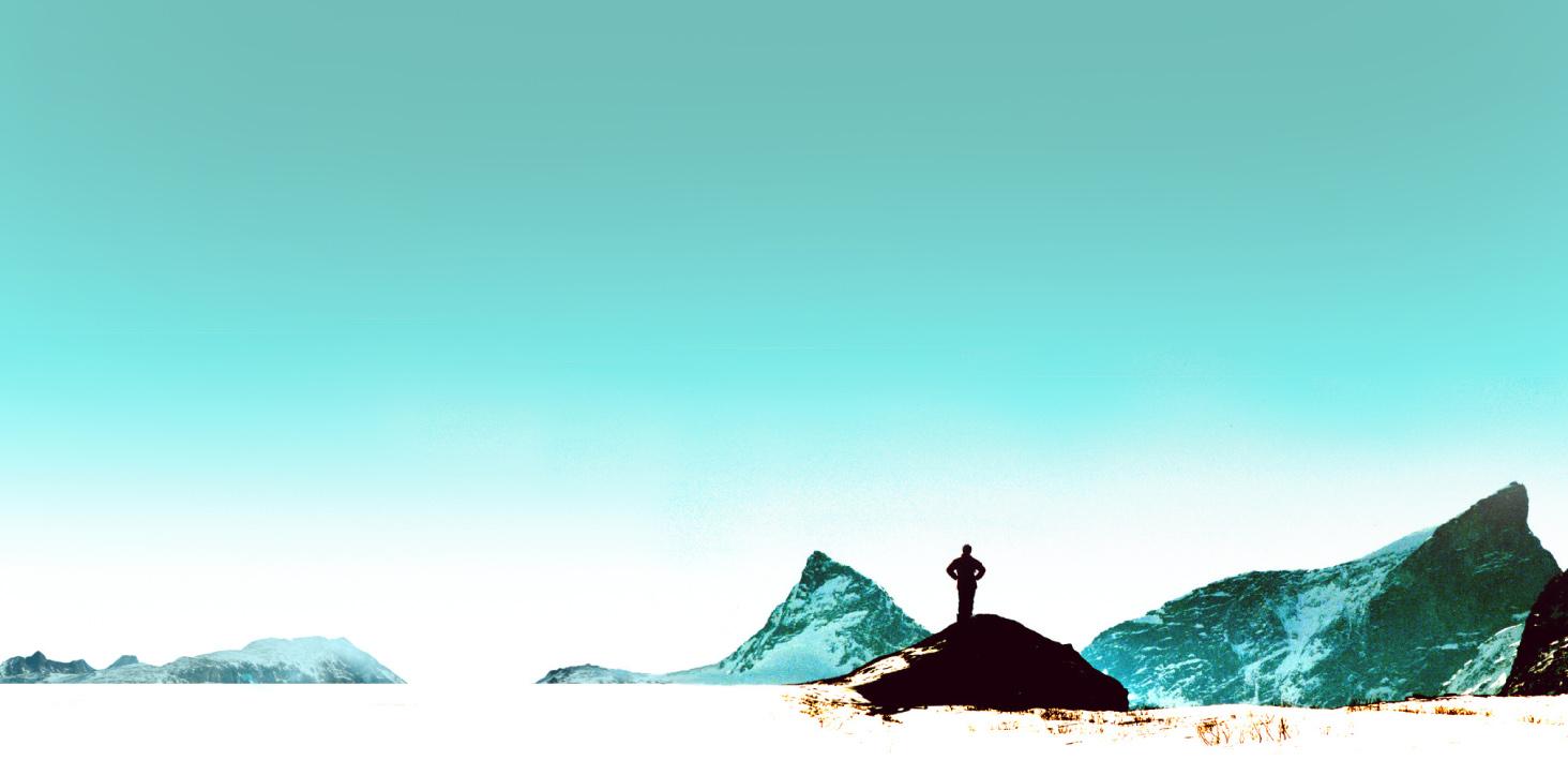 Foto med mann som står og ser utover horisonten i fjellheimen.